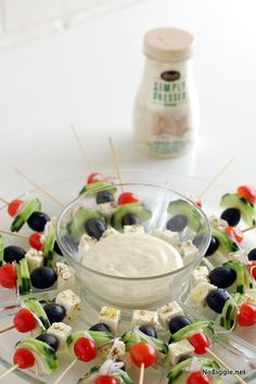 Greek salad skewers - tomato, cucumber, olive and seasoned feta on a stick. Love this presentation for a party. :)