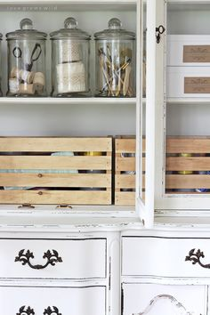 Glass Canisters from Hobby Lobby in - Old hutches and china cabinets make great storage for an office! See how this outdated piece gets transformed at LoveGrowsWild.com