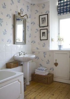 simple bath with a floral wallpaper that is easy to live with