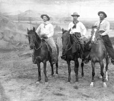 Three cowboys, including from left George Shanton, Jack Burke and Burt Schenck, pose on horseback in a dirt arena of the Wild West Show at Ambrose Park in Brooklyn, New York. 1894