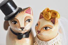 O dia do casamento é uma das datas mais marcantes na vida de um casal. Portanto, cada detalhe precisa ser cuidadosamente pensado para que as boas lembranças nunca se apaguem. Os gatinhos são feitos de papel machê, com detalhes de flores de fita de cetim na grinalda da noiva. O buquê é feito com flores secas e o véu da noiva com tule. A base redonda é de MDF.
