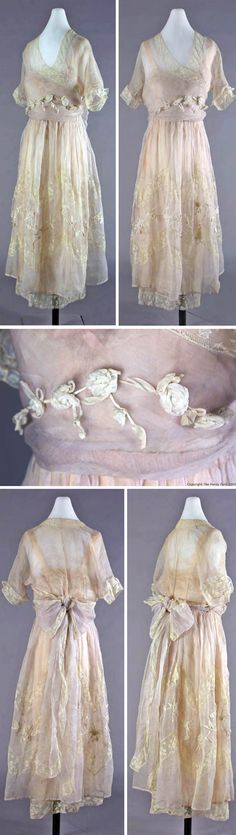 Dress (wedding?), Lucile, New York, ca. 1918. Light blue sheer silk over attached pink silk slip; 2-piece silk underslip. Eight-piece slip bodice is light pink silk w/cream cotton lace at neck & front. Pink satin ribbon straps. Underskirt of pink silk w/cotton lace ruffle & gauze. Sheer, heavy silk overskirt. Inset bands of lace w/cotton floral appliqué. Kimono sleeve overbodice w/cotton lace at neck & cuffs. Left bodice panel (w/floral appliqué) wraps over right. Detroit Historical Museum