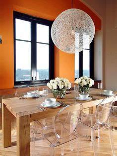 A rustic wooden table combined with iconic (and nearly invisible) Louis Ghost Chairs creates an interesting mix of textures in this penthouse dining room. Design by HGTV Star contestant Tylor Devereaux Wooden Dining Room Chairs, Dining Room Design, Dining Room Table, Orange Dining Room, Clear Chairs, Rustic Wooden Table, Ghost Chairs, Deco Design, Hgtv Star