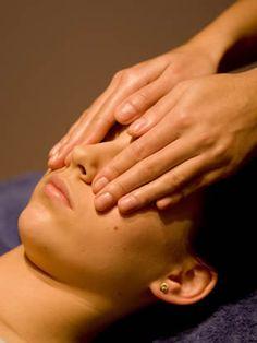 In this photo, the Reiki practitioner is giving Reiki to a person's face. The practitioner may place her hands above, or on various locations throughout the body.