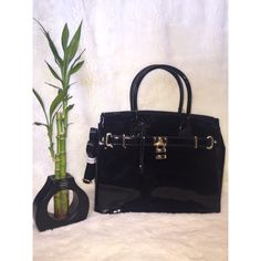 "Patent Lock Tote! Black Patent Lock Tote! NWT! ♥️ Product Dimensions:  Strap Drop - 5"" Height - 11 3/8"" Length - 13 6/8"" Width - 6""  Features: 4 pockets on the inside; cell phone (2), center pocket, and side pocket. A back pocket for easy access to items.  An adjustable over-shoulder strap.  Removable lock on the front.  Removable fab holder.  Feet on the bottom of the bag Would mostly be carried in the hand or worn on the arm, but strap is adjustable to be worn as a cross-body bag. Bags…"