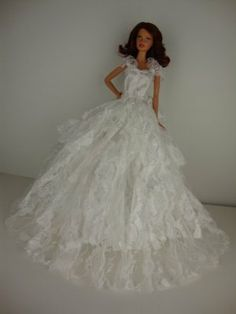 A Long White Lacy Gown with Attached Shoulder Wrap Made to Fit the Barbie Doll by Olivia's Doll Closet. $7.00. Please note: that all items are made for and or by Olivias Doll Closet, they are made to fit the popular Barbie Doll products. We are not affiliated with Mattel, we are not implying in any way that these items are associated with Mattel. We simply just offer great products to complement the Barbie products. Barbie is the trademark of Mattel. You will not be disappointe...