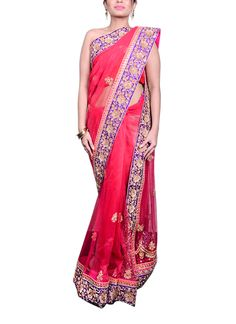 A gorgeous Saroj Jalan saree in a bright pink colour for the woman who wants to stand out even in a crowd. The rani pink net saree is festooned with golden butis all over, finished with an orange border with kundan work and a magenta raw silk border with zardosi embroidery all over. The saree is paired with a magenta raw silk blouse with golden thread work in floral designs.
