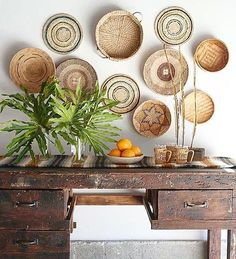 Isn't this the most amazing wall decor idea? I'm absolutely loving this decor and design. And just look at these cute African baskets above this rustic wooden table! Wall Decor, Decor, Home Decor Baskets, Basket Wall Decor, House Interior, Plates On Wall, Interior, Home Decor, Interior Decorating