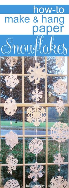 How to make and hang paper snowflakes in a window. #DIY #holidaydecorations