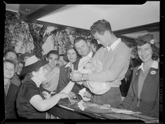 Jimmie Foxx and Ted Williams (both in civvies) surrounded by a crowd as Williams cradles an infant and a woman looks on.: 1939 - 1942