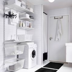 A utility room with white wall shelves, boxes in different sizes and a drying rack