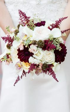 Rich colored wedding bouquet filled with roses, peonies, and orchids and marsala dahlias