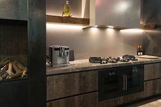 Massief Barnwood fronten, Marmer werkbladen Fior di Bosco, Pitt Cooking kookplaat, blauwstalen zijwanden, Gaggenau ovens, open haard vervaardigd uit blauwstaal, eiken houten schappen met waankant. Verlichiting onder en boven open schappen - The Living Kitchen B.V. by Paul van de Kooi