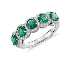 This ring features vivid green emerald gemstones surrounded by a halo of brilliant diamonds framed in 18k white gold.