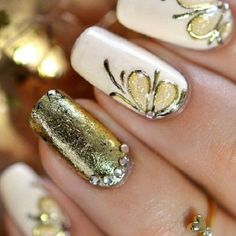 Elegant looking white and gold nail art design. The nails are designed with gold metallic polish over a white base as well as gold embellishments on top with flower designs and beads.