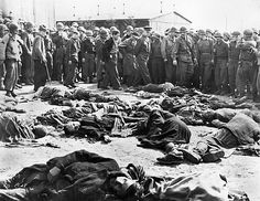 General Dwight D. Eisenhower, on a tour of the Third Army front, walks around a cluster of corpses representing the remains of many of the inmates of the German concentration camp at Gotha, Germany at the end of World War II, 12 April 1945.
