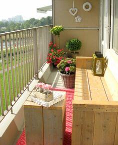 idee amenagement terrasse, balcon fleuri, banc long en poutres de bois avec une lanterne posée au bout, table en poutres de bois en forme carrée, tapis rouge et blanc, pots avec des fleurs rouges
