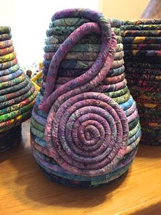 This fabric coiled pot is made from Anthology Bali Batiks in blues along with some other batiks I had on hand. The bottom starts at 9.5 and I coil the sides slowly outward to about 12. Then I take it back in and up to a height of 14. The opening at that height is 5. I continue the coil down and around to create a design on the side of the pot and focus it mainly on the purples. Bottom:12  Sides:12  Height:14 Making Baskets, Coil Pots, Rope Basket, Clothes Line, Trending Outfits, Purple, Crochet, Unique Jewelry, Handmade Gifts