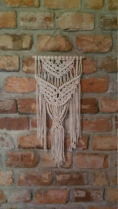 Made with white, twisted cotton rope. I just love this material--it does great with knotting! Really sturdy and durable. Easy to pick up and move around when you are trying to find the perfect place to hang it! Approx. Dimensions W:12in. H: 27in. * made-to-order items may vary