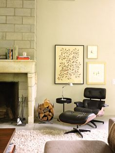 Modern and cozy living room, stone fireplace, Eames lounge chair, Marcel Dzama art....my daughter has this chair and wants to recover it. She wondered how it would look in dark leather.