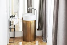 Cylindrical brass and porcelain sink at the Senato Hotle, Milano. Design by Alessandro Bianchi.