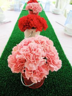 Carnations in buckets on a fake grass runner