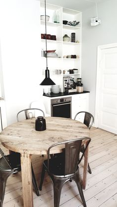White kitchen with earthy round wooden table and open shelving displayinga range of beautiful ceramics Scandinavian Apartment, Scandinavian Home, Modern Rustic Homes, Nordic Living, Wooden Dining Tables, Apartment Kitchen, Rustic Industrial, Open Shelving, House Design