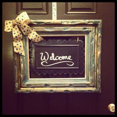 Welcome door hanger I made from a yard sale 1970s frame that I paint washed, deal of the day kirklands chalkboard, and burlap ribbon