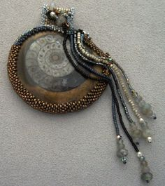 Take an ammonite in rich greys and muted browns.  Add to it seed beads in greys and black, labradorite rondelles, freshwater pearls and moonstone rondelles and look what you get.