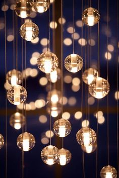 Plastic ornaments filled with LED tea lights suspended from fishing line for Christmas decor.
