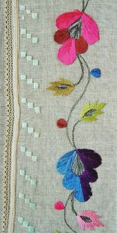 A detail of a large embroidered headscarf, Crimean Tatar, probably from Romania, c. 1900. Called 'marama'. Embroidered on cotton (organdy), 70 x 178 cm. A meandering stem, interrupted by stylized flowers, with smaller buds and small leaves attached to the main stem. Light blue border worked in counted-thread style. All embroidery in mercerized cotton & metallic (silver) thread.  Embroidery height (from the tip of petals to the edge of cloth): 9 cm. (The Asiye-Zeynep Collection, Washington…