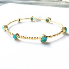 Julie Vos Gold and Turquoise Ribbed Bangle This 24 karat gold plated ribbed bangle has 7 turquoise stones, both round and oblong. This looks awesome by itself but even better stacked! The turquoise really pops! Julie Vos Jewelry Bracelets