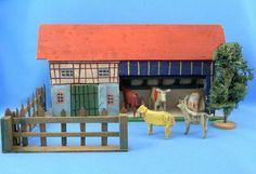 Antique German Erzgebirge wooden barn with animals.  Probably handcrafted in the Erzgebirge region, early 20th century.  The barn has 4 stalls, a hay rack and a door.  Barn overall 9-1/8 in L x 2-1/8 in W x 4-3/4 in H