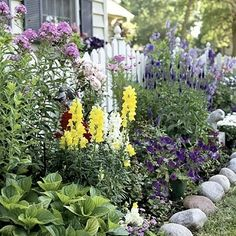 so many great layers!  the picket fence, layered flower bed and soft rock border.  BHG.com country garden slideshow by ofelia