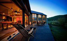 夕景、山に日が沈み内部の色壁や照明が暖かく浮かびあがる: UZUが手掛けた家です。