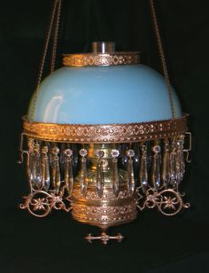 This is a beautiful antique Miller hanging oil lamp. The lamp has a powder blue Bristol shade. The lamp has a row of blue crystal prisms around the shade ring and font holder. The lamp has a Miller centerdraft font. Victorian Lighting, Victorian Lamps, Antique Lighting, Antique Light Fixtures, Antique Oil Lamps, Vintage Lamps, Vintage Antiques, Kelly Wearstler, Hurricane Oil Lamps
