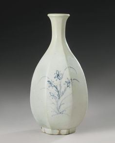 A KOREAN BLUE AND WHITE FACETED BOTTLE VASE JOSEON DYNASTY, 18TH CENTURY of ovoid form with eight facets, the narrow neck flaring to a lipped rim, freely painted in underglaze-blue with sprays of asters and orchids, supported on a gently tapered foot, Japanese wood box (4) Height 9 1/4  in., 23.5 cm