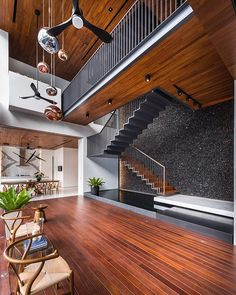 A three-story steel staircase, backdropped by a feature wall of black pebbles, floats above a koi pond at a daylight-filled Singapore residence by @ming_architects. : Edward Hendricks. @sandow