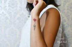 Flower tattoo on the left wrist.