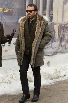 Shop this look on Lookastic: https://lookastic.com/men/looks/parka-shawl-cardigan-long-sleeve-shirt-jeans-chelsea-boots-sunglasses/6062 — Black Sunglasses — Black Long Sleeve Shirt — Olive Shawl Cardigan — Olive Parka — Black Jeans — Black Leather Chelsea Boots