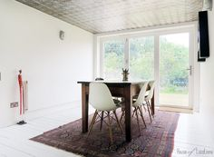 the dining end of my kitchen madaboutthehouse.com #paintedfloorboards #tinceiling faded rug #eameschairs and old school table