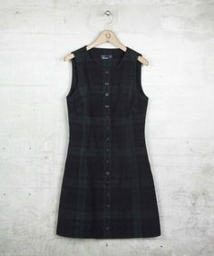 Button through pinafore dress crafted in a cotton baby cord fabric, complemented by traditional Black Watch Tartan and a button through design. With a subtle A line cut and flattering curved neckline, this cotton corduroy pinafore dress is perfect paired