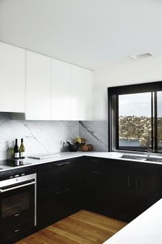Kitchen: white handleless wall cabinets, black floor cabinets, marble splashback, thin white marble benchtop, timber window frames painted black, timber floorboards, water views