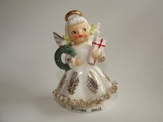 The 526 series of angels is characterized by halos floating away from the head, big wings with gold highlights, an A-line gown sponged with gold and trimmed with gold-touched spaghetti at the skirt edge and the edge of the sleeves, pigtails and colored hair-bows, and that winsome face. This angel has all those features, and a lovely patina to her face. Her wreath is a lighter Christmas green with red holly berries painted on it, and she holds a rectangular gift wrapped in red ribbon, with…