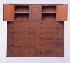 A massive tool cupboard made around 1840, when Shaker design was at its purest and most abstract, carefully fits form to function. This shallow cupboard, designed to store woodworking tools, is unusual for its size, asymmetrical layout, arrangement of doors, and use of contrasting colored finishes.