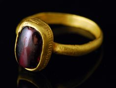 Gold and garnet medieval or byzantine ring. High karat gold ring, the oblong bezel is set with a perforated convex garnet, probably previously used as a pearl. The lower part of the bezel adorned with a limed beaded line. The hoop is flat inside and rounded outside, welded under the bezel.  Byzantine or barbarian art, early medieval, 5th-6th century AD