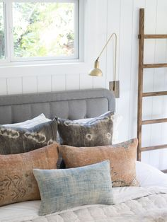 layered vintage pillows, neutral bedding, decorative ladder, brass cafe arm sconces, vertical wall paneling shiplap