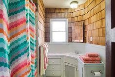 Used on interior walls, cedar shakes lend a charming, cottage-style feel while adding visual interest. A colorful shower curtain and bright white vanity keep the small bathroom looking fresh and updated. Tiny Bathrooms, Beach Bathrooms, Small Bathroom, Bathroom Ideas, Bathroom Organization, Cedar Shake Siding, Cedar Shakes, Colorful Shower Curtain, Cozy Basement