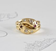 A wonderful antique English double-headed snake ring crafted in 18k yellow gold set with sparkling old mine-cut diamonds along the top of each head and ruby eyes, letter dated for 1902. Twined and linked the two snakes face in opposite directions forming a double banded effect all around the shank; thick and comfortably smooth the ring is beautifully crafted with a satisfying weight on the hand. A centuries old reference to eternal love and faithfulness. Perfect for stacking, worn alone or…