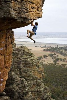 DANGEROUS SPORTS - ROCK CLIMBER HANGS ON TO OVERHANG - SCARY